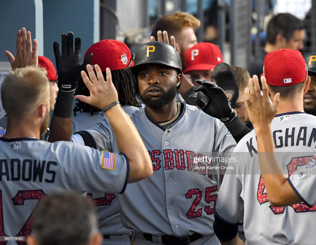 Gregory Polanco #25 of the Pittsburgh Pirates is congratulated in the dugout after hitting a two-run home run in the eighth inning of the game off Edward Paredes #58 of the Los Angeles Dodgers at Dodger Stadium on July 4, 2018 in Los Angeles, California.