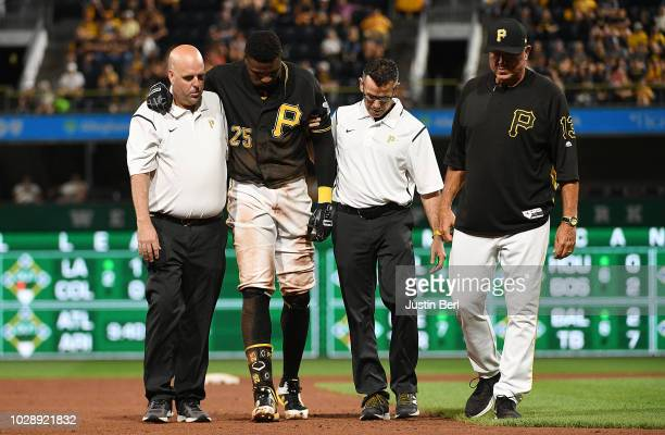 Gregory Polanco of the Pittsburgh Pirates is walked off by field by trainers Bryan Housand and Ben Potenziano after being injured on a slide attempt...
