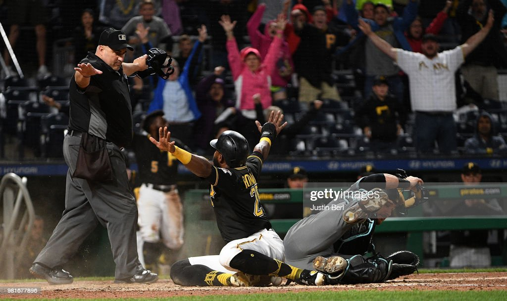 Gregory Polanco #25 of the Pittsburgh Pirates reacts after he slid into home plate past Jeff Mathis #2 of the Arizona Diamondbacks to score a run in the eleventh inning during the game at PNC Park on June 22, 2018 in Pittsburgh, Pennsylvania.
