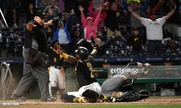 Gregory Polanco of the Pittsburgh Pirates reacts after he slid into home plate past Jeff Mathis of the Arizona Diamondbacks to score a run in the...