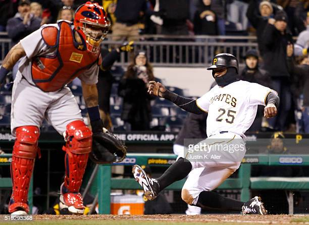 Gregory Polanco of the Pittsburgh Pirates slides in safe on a eleventh inning RBI single during the game against the St Louis Cardinals at PNC Park...