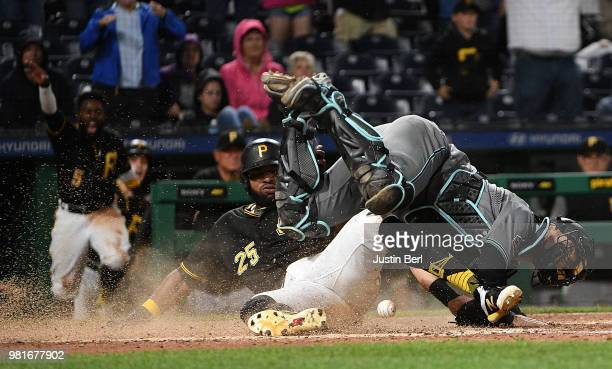 Gregory Polanco of the Pittsburgh Pirates slides into home plate past Jeff Mathis of the Arizona Diamondbacks to score a run in the eleventh inning...