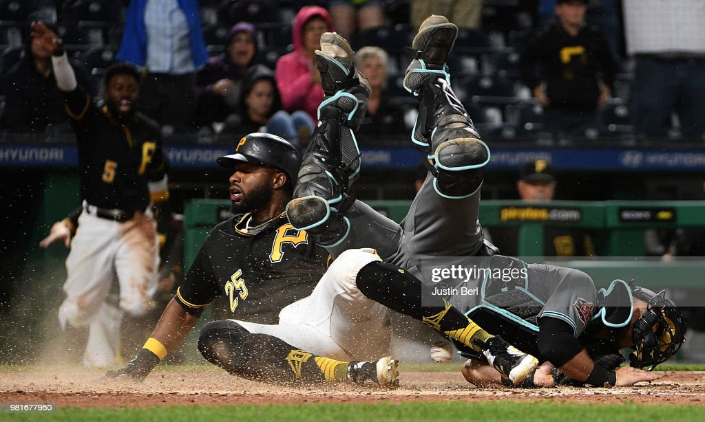 Gregory Polanco #25 of the Pittsburgh Pirates slides into home plate past Jeff Mathis #2 of the Arizona Diamondbacks to score a run in the eleventh inning during the game at PNC Park on June 22, 2018 in Pittsburgh, Pennsylvania.