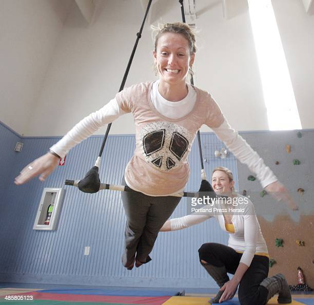 Assisted by Casey Turner Jill Newell finds her balance point on a trapeze during an aerial apparatus workshop at the Breakwater School in Portland on...