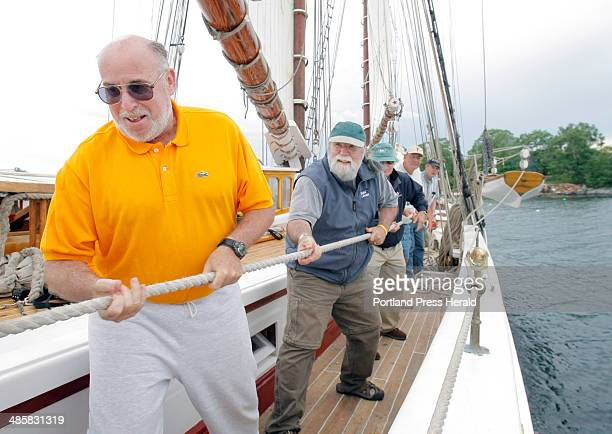 Gregory Rec/Staff Photographer Harvey Rubin left and Frank Hamilton along with other passengers aboard the schooner Heritage pull in the main sail...