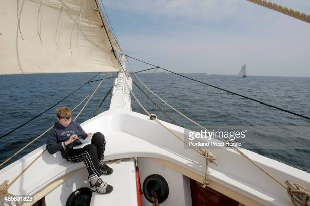 Gregory Rec/Staff Photographer Jonathan Tobin a passenger aboard the schooner Heritage looks through a bird identification book in the bow of the...