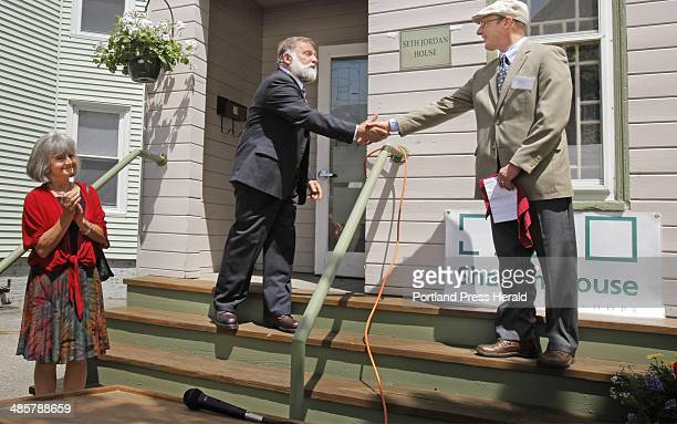 Mark Adelman right< of Shalom House shakes hands with Bob Jordan after Jordan unveiled the plaque at the Seth Jordan House in Portland on Friday May...