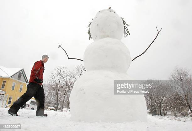 Nate Ruel carries rocks to be used as eyes and buttons on a 7foot tall snowman he built along Day Street in Kennebunk on Friday April 1 2011 The...