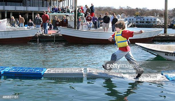 Gregory Rec/Staff Photographer Simon Spear makes his second run across lobster crates at the 35th annual Fishermen's Festival in Boothbay Harbor on...