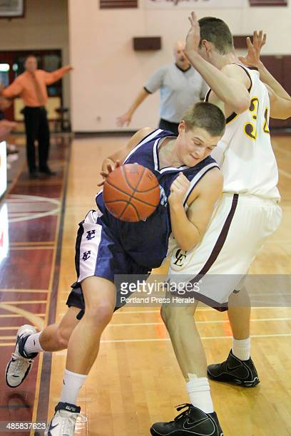 Gregory Rec/Staff Photographer -- Yarmouth's Johnny Murphy drives past Cape's Ben Fox at Cape Elizabeth High School on Tuesday, February 3, 2009.
