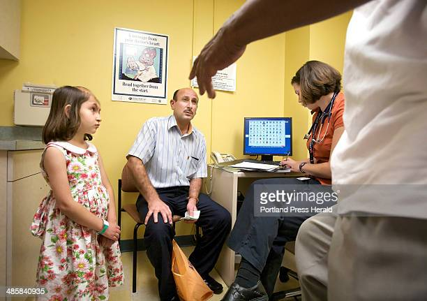 A Afif Abdulhameed Otaiwi talks to an interpreter during a doctor's appointment for his daughter Noora at left in the pediatric clinic at Maine...