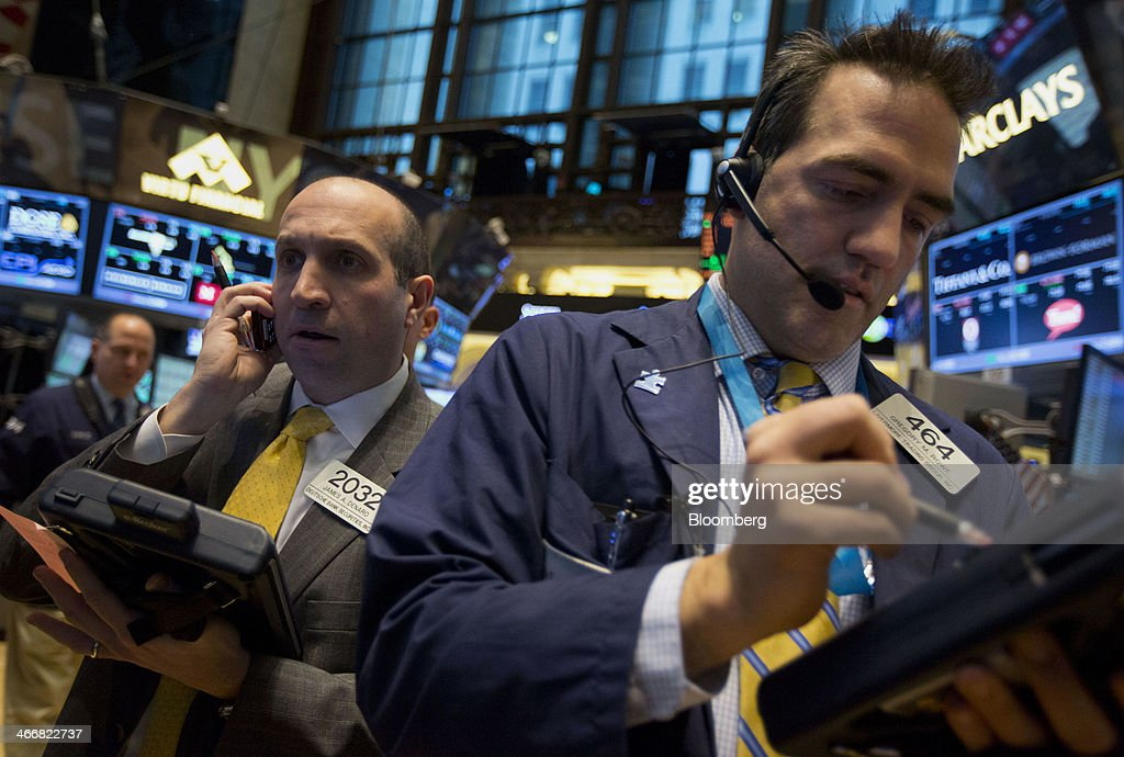 Gregory Rowe, a trader with Livermore Trading Group Inc., right, works on the floor of the New York Stock Exchange (NYSE) in New York, U.S., on Tuesday, Feb. 4, 2014. U.S. stocks rose, with the Standard & Poor's 500 Index rebounding after the biggest drop since June, as Treasuries retreated and South Africa's rand led emerging-market currencies higher. Photographer: Jin Lee/Bloomberg via Getty Images