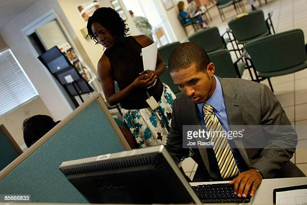 Gregory Tai who lost his job working in marketing fills out a form on the computer while he waits for a job interview as he competes with others for...