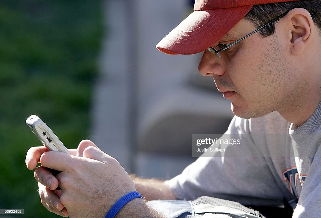 Gregory Vickrey uses a Blackberry while sitting in Union Square February 24, 2006 in San Francisco. A federal judge delayed a ruling on an injunction request by BlackBerry maker Research in Motion, who is seeking to prevent the service from shutting down over a patent dispute.