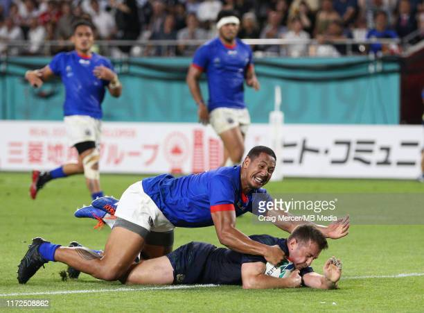 Greig Laidlaw of Scotland scores his sides second try despite the tackle of Ed Fidow of Samoa during the Rugby World Cup 2019 Group A game between...