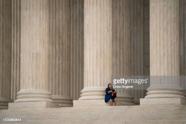 Greisa Martinez who grew up as an undocumented immigrant in Dallas Texas sits on the top steps of the Supreme Court while awaiting a decision to be...