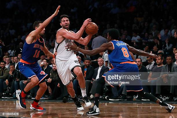 Greivis Vasquez of the Brooklyn Nets drives in the lane as he is defended by Sasha Vujacic and Justin Holiday of the New York Knicks during the first...