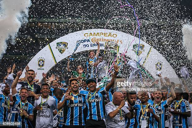 TOPSHOT Gremio players celebrate with the Brazil Cup 2016 trophy after winning over Atletico Mineiro at Arena do Gremio in Porto Alegre Brazil on...