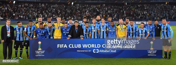 Gremio players pose with their silver medals following the Club World Cup final football match against Real Madrid at Zayed Sports City Stadium in...