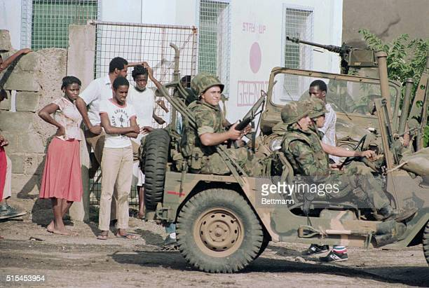 A group of United States combat soldiers drive past Grenada residents in a jeep during the United States invasion of the island of Grenada