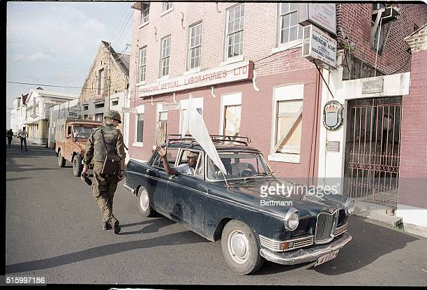 An automobile drives past a United States soldier and the Swedish Embassy in Grenada during the United States invasion of the island of Grenada