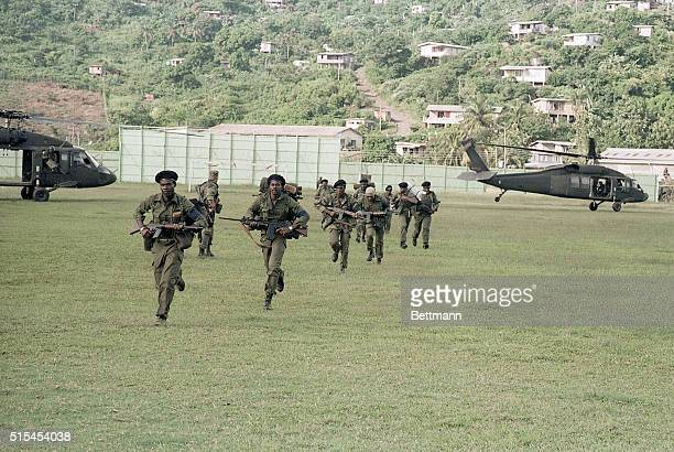 United States combat soldiers run across a soccer field from where their helicopter set them down during the United States invasion of the island of...