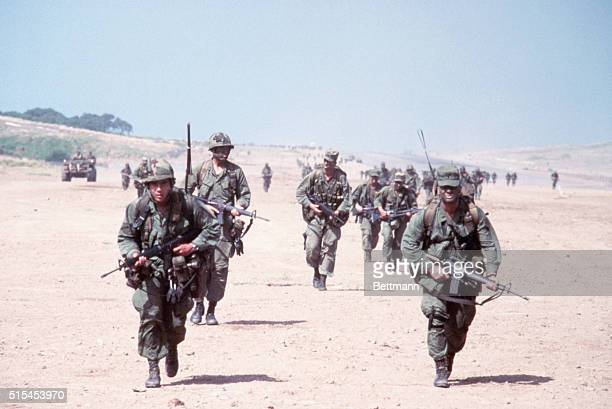 United States combat soldiers run in parallel lines across an empty dirt field with their rifles at ready during the United States invasion of the...