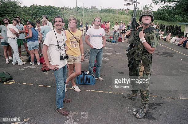 United States medical students to be evacuated from the island of Grenada stand with an armed United States soldier looking up while waiting their...