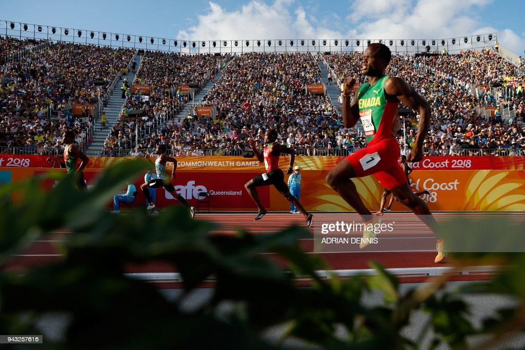 TOPSHOT - Grenadas Bralon Taplin (R) competes in the athletic's men's 400m heats during the 2018 Gold Coast Commonwealth Games at the Carrara Stadium on the Gold Coast on April 8, 2018. / AFP PHOTO / Adrian DENNIS