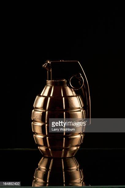 a grenade on a shiny surface, black background - hand grenade stock pictures, royalty-free photos & images