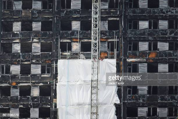 Grenfell Tower is partially covered by a white plastic sheet as work began this week to cover the ruins on October 15 2017 in London England The...