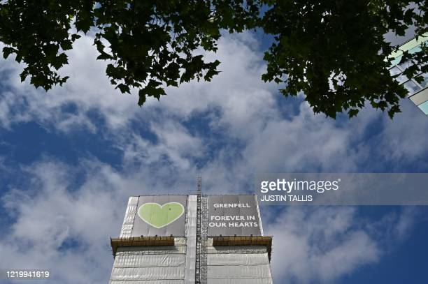 Grenfell tower is seen covered in a safety tarpaulin in west London on June 14 on the third anniversary of the highrise fire that killed 71 people...