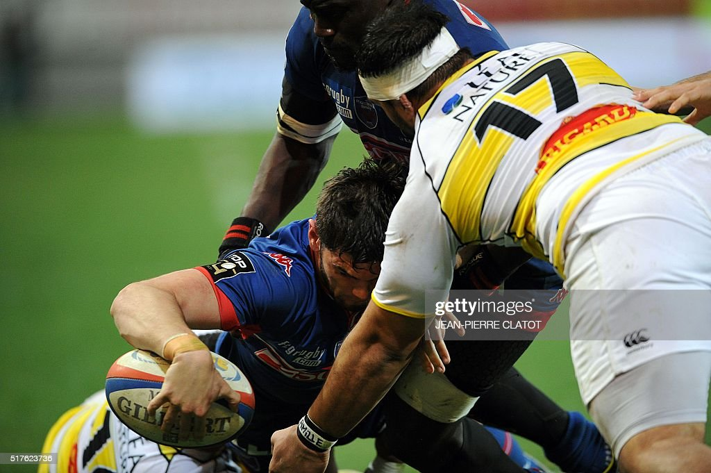 Grenoble's French centre Xavier Mignot (L) scores a try during the French Top 14 rugby union match between Grenoble and La Rochelleon march 26, 2016 at the Stade des Alpes in Grenoble.