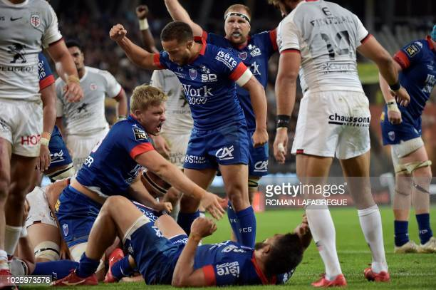 Grenoble's French flanker Antonin Berruyer celebrates with teammates after try by Grenoble's Portuguese hooker Mike Tadjer during the French Top 14...