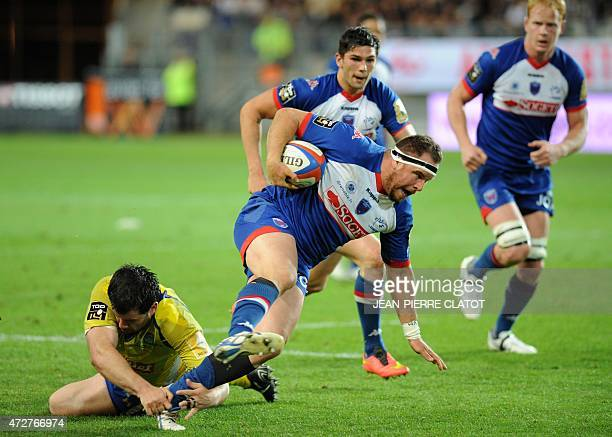 Grenoble's French prop Laurent Bouchet is tackled during the French Top 14 rugby union match Grenoble vs Clermont on May 9 2015 at the Stade des...