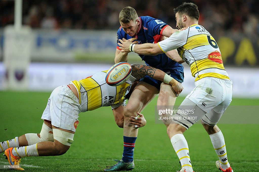 Grenoble's Irish centre Chris Farrell (C) vies with La Rochelle's French lock Romain Sazy during the French Top 14 rugby union match Grenoble (FCG) vs La Rochelle (ASR) on March 26, 2016 at the Stade des Alpes in Grenoble.