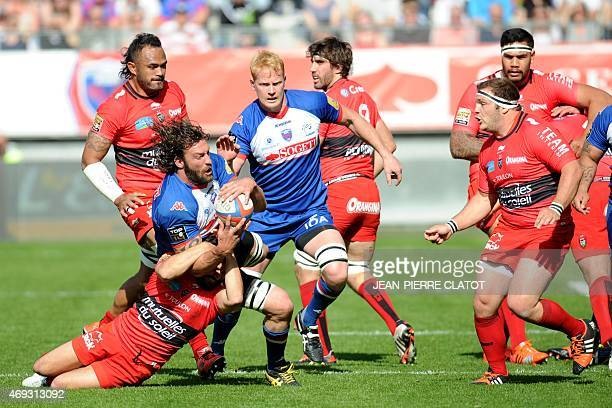 Grenoble's South African lock Ross Skeate is tackled by RCToulon's French scrumhalf Eric Escande during the French Top 14 rugby union match Grenoble...