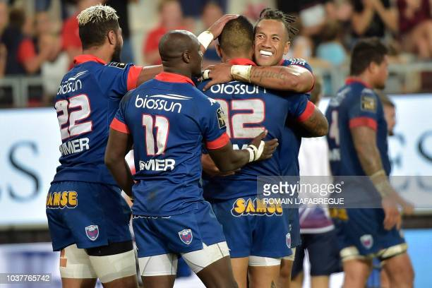 Grenoble's South African wing Raymond Rhule celebrates with teammates after scoring a try during during a French Top 14 rugby union match between...