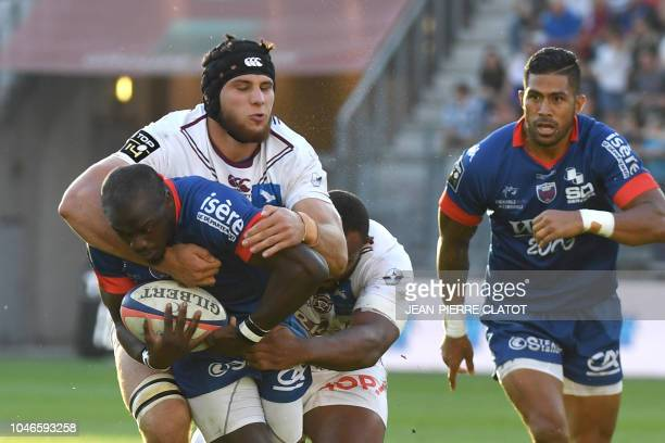 Grenoble's South African winger Raymond Rhule is tackled by BordeauxBegles' French lock Cyril Cazeaux during the French Top 14 rugby union match...