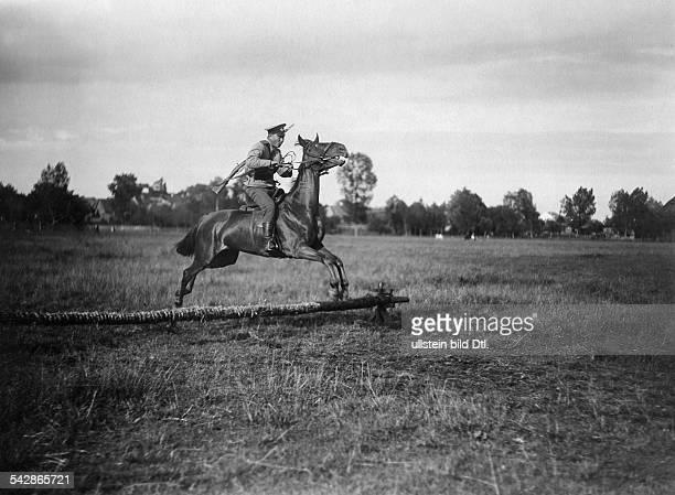 Grenzstation an der deutschrussischen Grenze Kosak springt mit seinem Pferd über eine Hürde undatiert vermutlich um 1910Foto Conrad HünichFoto ist...