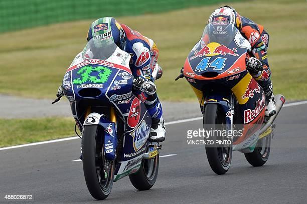 Gresini Racing Team Moto3's Italian rider Enea Bastianini rides ahead of Red Bull KTM Ajo's Portuguese rider Miguel Oliveira during the Moto 3 race...