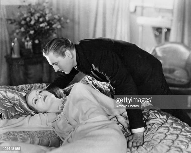 Greta Garbo in bed as John Barrymore is about to join her in a scene from the film 'Grand Hotel' 1932