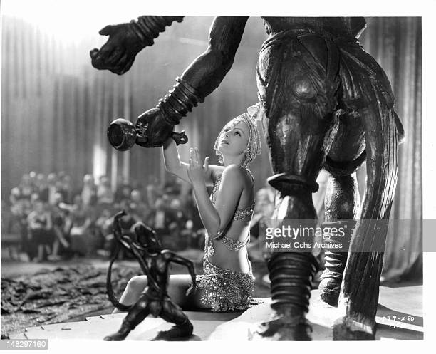 Greta Garbo sitting underneath an ancient statue while wearing a ornate halter dress in a scene from the film 'Mata Hari' 1931