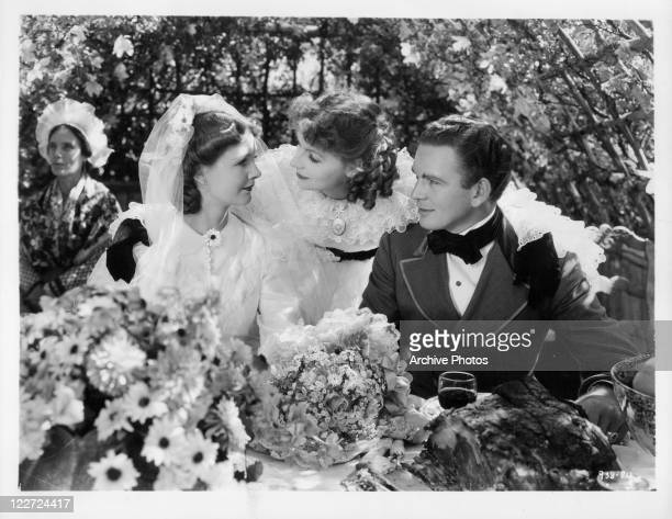 Greta Garbo with arms around Elizabeth Allan and Robert Taylor in a scene from the film 'Camille' 1936