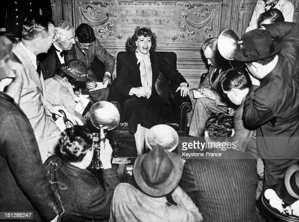 Greta Garbo with photographers swarming around her in a lounge on the Gripsholm' ocean liner which was bringing her back to the United States after a...