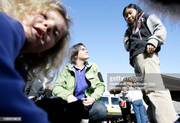 Gretchen Miller watches and answers question about Tanner a Boulder Humane Society dog while Angela Sakai helps and sisters Kate and Emily Jader play...
