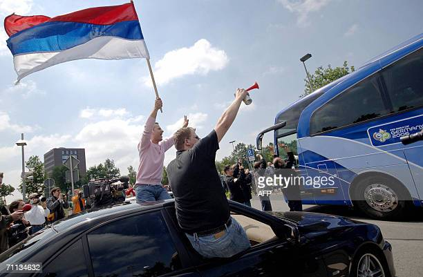 Supporters of the Serbia and Montenegro national football team wave a Serbian flag upon the arrival of the team 06 June 2006 in Greven Serbia and...