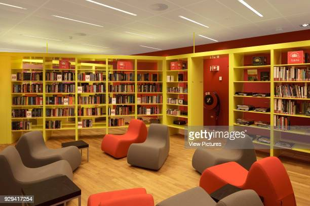 Grey and orange chairs with yellow bookshelves against red wall on first floor