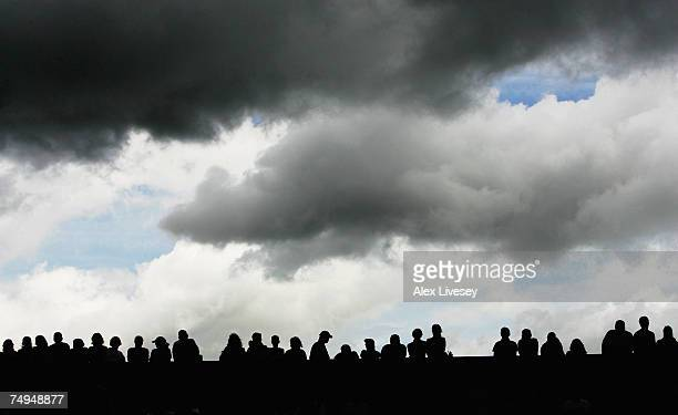 Grey clouds move over number two court raise their umbrellas as the rain arrives during day five of the Wimbledon Lawn Tennis Championships at the...