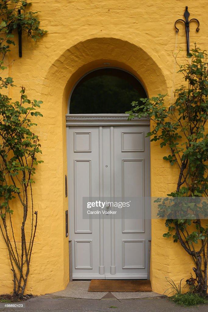 Grey door on a dark yellow house : Stock Photo